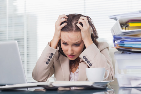 Nervous businesswoman pulling her hair out in her bright office photo