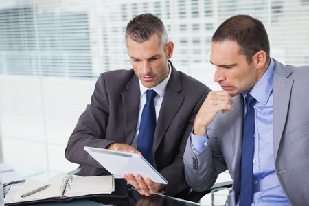 Concentrated businessmen analyzing documents on their tablet in bright office photo