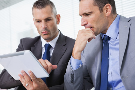 Focused businessmen analyzing documents on their tablet in bright office photo