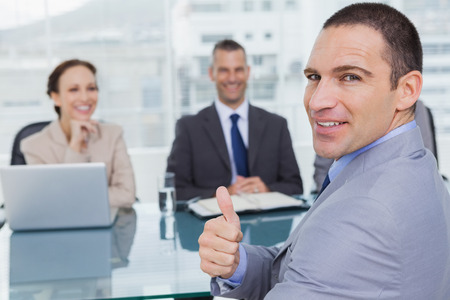 obtaining: Applicant giving thumb up after obtaining the job in bright office Stock Photo