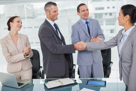Smiling future workmates shaking hands in bright office photo