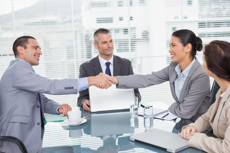 Smiling business people shaking hands in bright office photo
