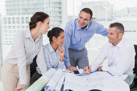 asian architect: Architects anaylzing plans together in bright office Stock Photo