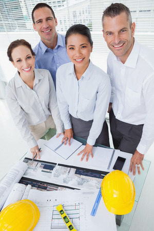 Smiling architect team posing while working together in bright office photo