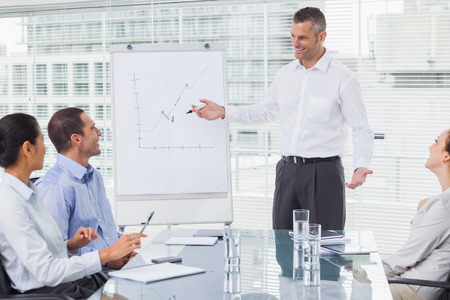 Smiling businessman giving presentation to his colleagues in bright office photo
