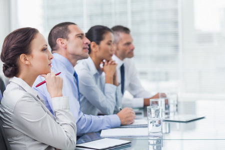 Thoughtful coworkers listening to presentation in bright office photo