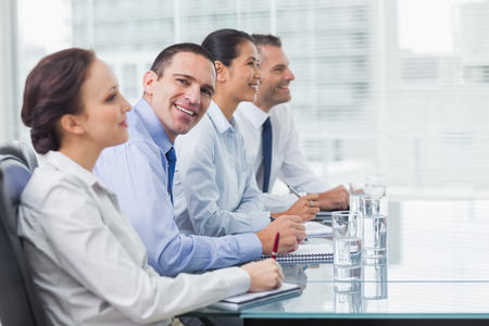 Businessman  in bright office smiling at camera while his colleagues listening to presentation photo