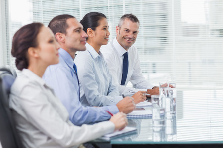 Businessman  in bright office smiling at camera while his colleagues listening photo