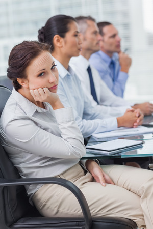 Bored businesswoman looking at camera while attending presentation in bright office photo