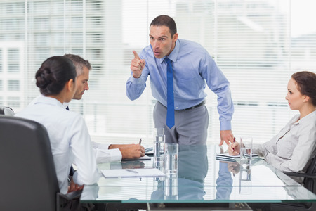 angry boss: Angry executive pointing out his employee in bright office Stock Photo