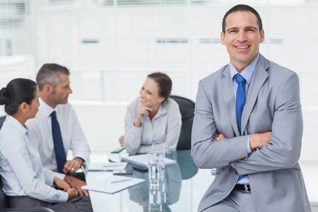 Smiling businessman in bright office posing while workmates talking together photo