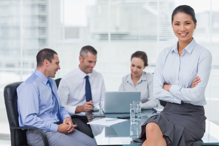 Smiling businesswoman in bright office posing while workmates talking together photo