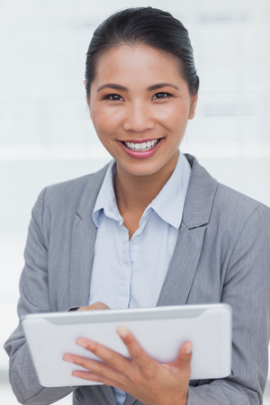 Smiling businesswoman in bright office posing scrolling on her tablet pc photo