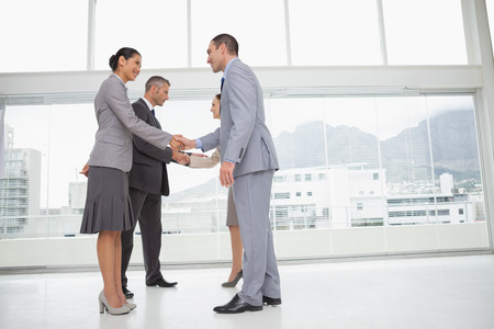 Business people meeting in bright office shaking hands photo