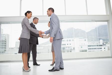 dandose la mano: Hombres de negocios reunidos en la Oficina brillante estrechar la mano