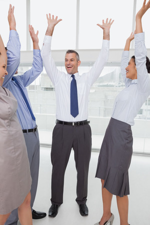 Work team cheering  together in bright office photo