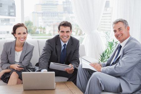 Business people smiling at camera while having a meeting in cosy meeting room photo