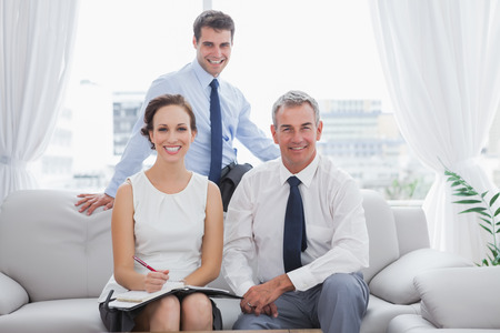 Cheerful partners posing while having a meeting in cosy meeting room photo