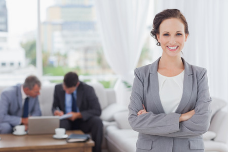 business attire: Cheerful businesswoman posing while her colleagues are working in bright office