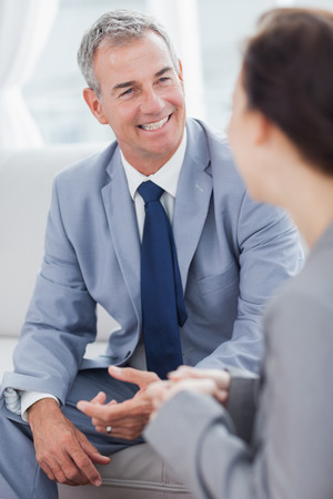 people interacting: Smiling businessman talking to his workmate in bright office