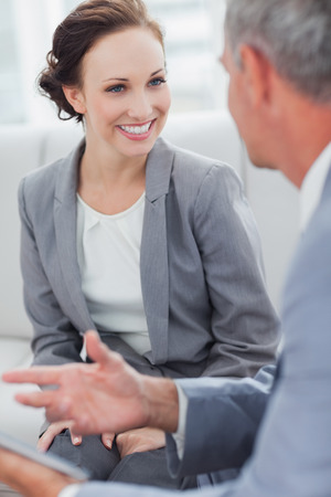 Smiling businesswoman listening to her workmate talking in bright office Stock Photo