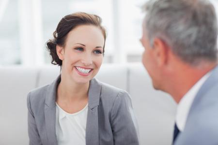 Vrolijke zakenvrouw luisteren naar haar workmate praten in heldere kantoor Stockfoto