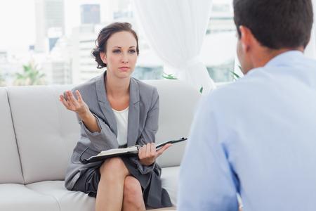 gefesselt: Serious Geschäftsfrau, die ihrem Kollegen in gemütlichen hellen Büro