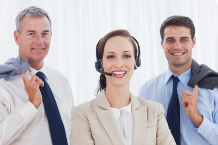 Cheerful call center agent posing with her work team in bright office photo