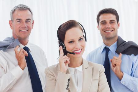 call center agent: Sorridente agente di call center in posa con il suo team di lavoro in ufficio brillante