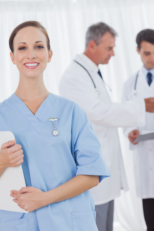 Cheerful surgeon posing while doctors talking on background in bright office photo