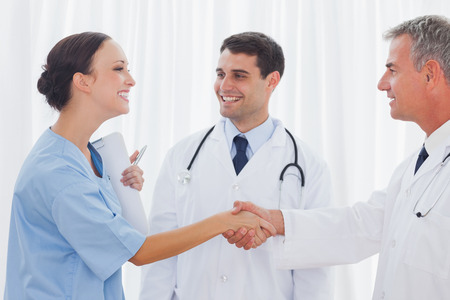 Surgeon in bright office thanking the doctor for helping her photo