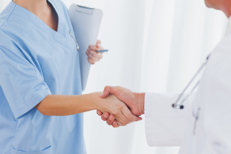 Close up on surgeon and doctor shaking hands in bright office photo