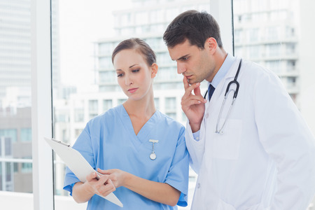 Focused surgeon and doctor working together in bright office photo