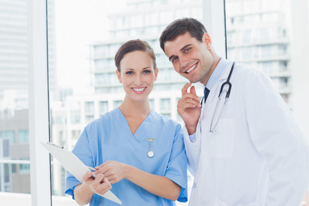 Cheerful surgeon and doctor posing while working together in bright office photo