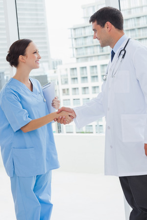 Doctor shaking hands with his new surgeon in bright office photo