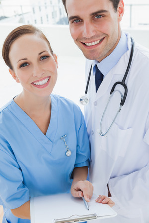 Smiling doctor and surgeon in bright office posing while holding documents together photo