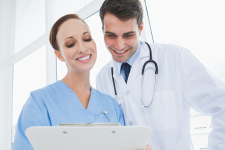 Cheerful doctor and surgeon viewing documents together in bright office photo