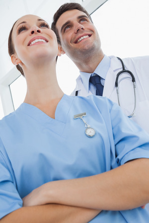 Smiling doctor and surgeon in bright office looking away photo