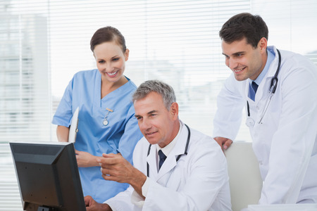 doctor computer: Doctors and surgeon working together on computer in bright office