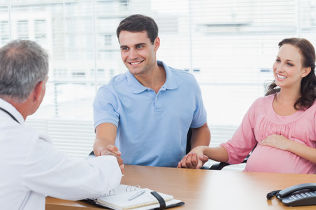 Smiling man shaking hands with his doctor while holding his expecting wifes hand in bright surgery photo