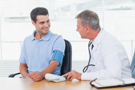 doctor appointment: Doctor taking blood pressure of smiling patient in bright surgery