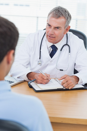 doctor patient: Serious doctor prescribing drug to his patient in bright surgery