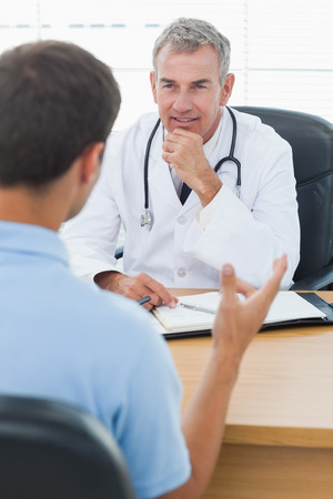 medico y paciente: Doctor atento que escucha a su paciente en la cirugía brillante Foto de archivo