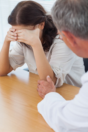 man sad: Upset patient crying while doctor comforting her in bright surgery Stock Photo