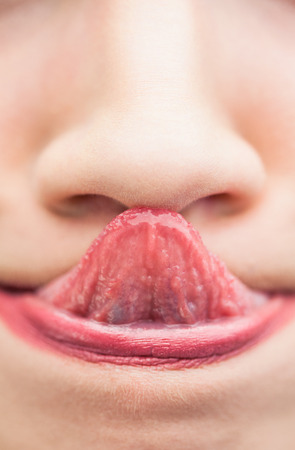 Extreme close up on natural woman touching her nose with her tongue photo