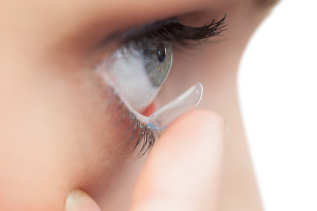 eye lens: Extreme close up on young model applying contact lens on her blue eyes