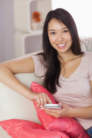 Happy asian girl using her smartphone on the couch looking at camera at home in the living room photo