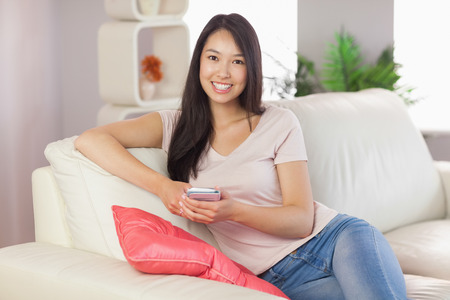 Pretty asian girl using her smartphone on the couch smiling at camera at home in the living room photo