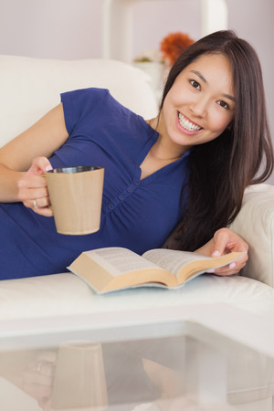 Smiling asian girl lying on the sofa reading a novel and drinking hot beverage in living room at home photo