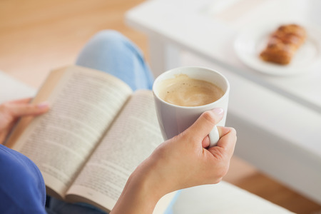 woman reading book: Woman sitting on the sofa reading a book holding her coffee mug in living room at home
